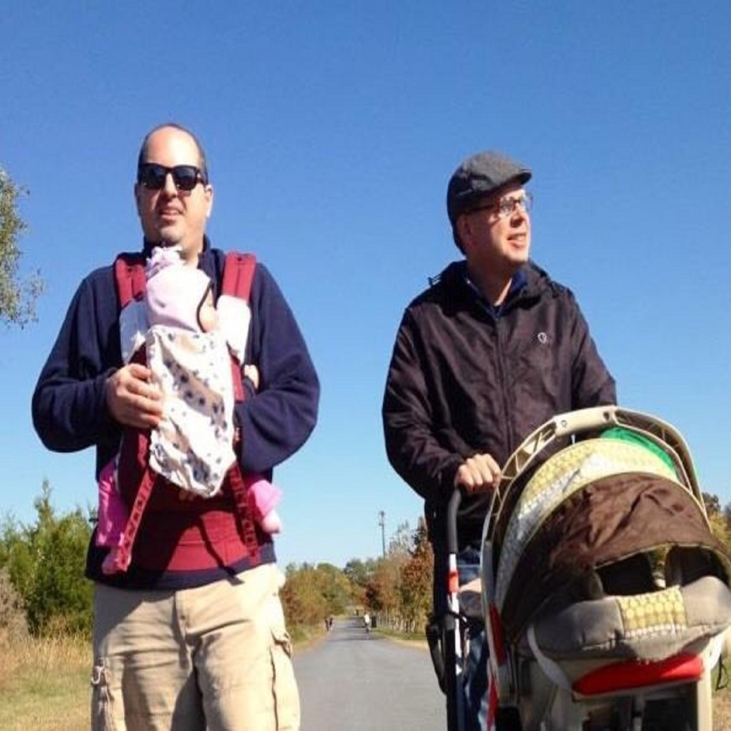 Two 30-something men stand side-by-side, Evan with his daughter in a sling, and Tony with his son in a stroller.